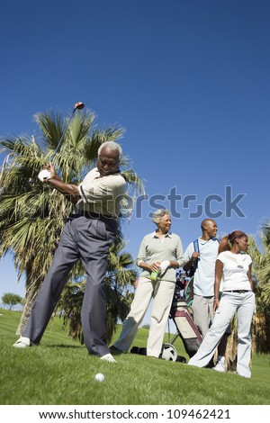 Full length of an African American man playing golf with family in background - stock photo