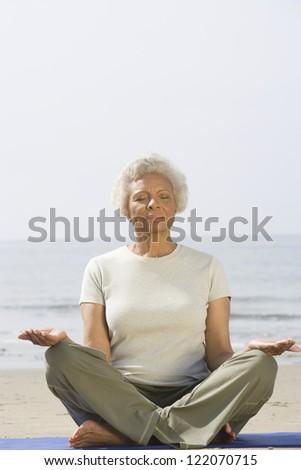 Full length of an African American senior woman meditating at beach - stock photo