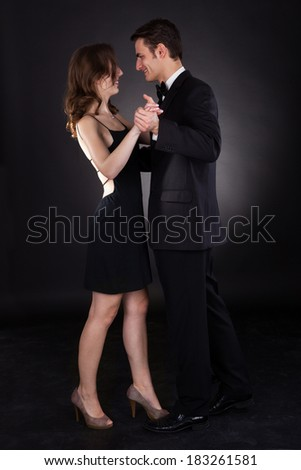 Full length of an elegant couple dancing together isolated over black background