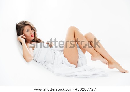 Full length of attractive alluring young woman lying wrapped in sheet over white background - stock photo