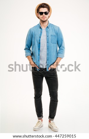 Full length of attractive confident young man in hat standing with hands in pockets over white background - stock photo