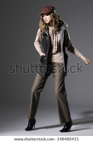 Full length of Attractive fashion model in hat posing on gray background d