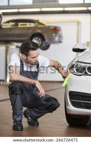 Full length of automobile mechanic cleaning car in workshop - stock photo