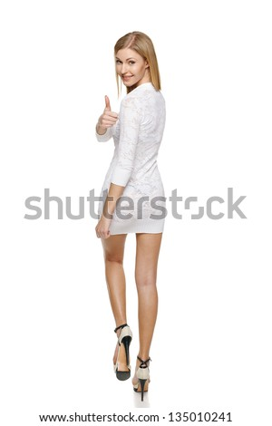 Full length of back view of walking woman showing thumb up sign over her shoulder - stock photo