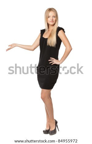 Full length of beautiful blond business woman in black dress showing copy space over white background - stock photo