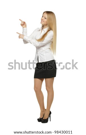 Full length of beautiful blond business woman pointing at copy space over white background - stock photo
