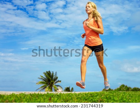 Full length of beautiful female athlete jogging on sidewalk at beach - stock photo