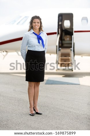 Full length of beautiful stewardess standing against private jet at terminal - stock photo