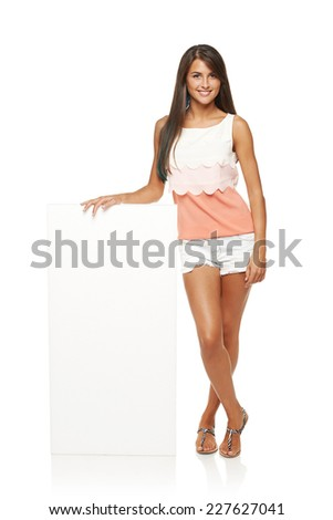 Full length of beautiful tanned woman in shorts standing leaning on white blank advertising board banner, over white background - stock photo