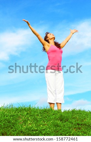 Full length of beautiful with arms raised giving glory to God. - stock photo