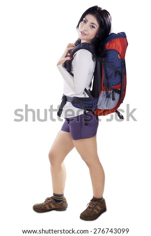 Full length of beautiful woman standing in the studio while carrying a backpack for hiking