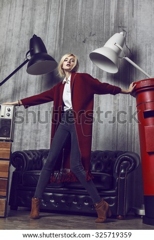 Full length of beautiful young blond woman wearing long red coat. Her hair is tied into fashion ponytail and fresh natural make up suit to the style. Composition is fill with lamps, sofa and retro tv  - stock photo