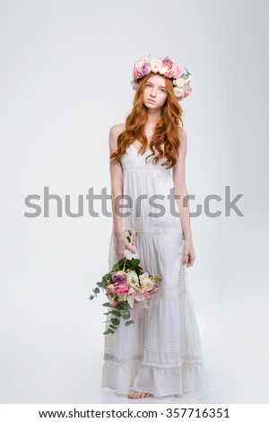 Full length of beautiful young redhead woman in white sundress and wreath standing barefoot and holding bouquet of flowers over white background - stock photo