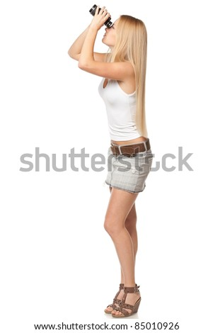 Full length of blond woman looking through binoculars upwards over white background, side view - stock photo