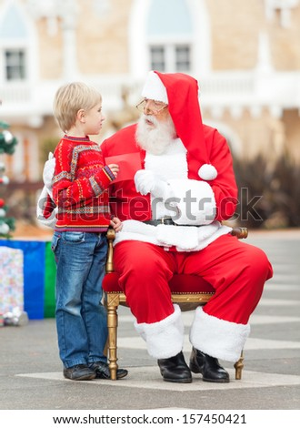 Full length of boy giving wish list to Santa Claus in courtyard - stock photo