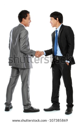 Full length of business colleagues shaking hands and smiling - stock photo