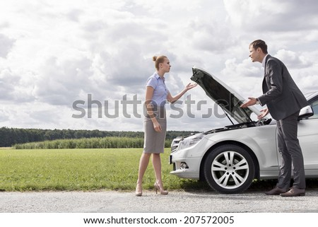 Full length of business couple arguing by broken car at countryside - stock photo