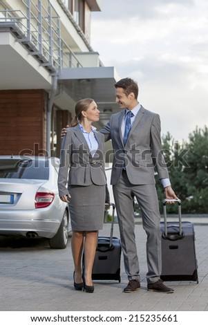 Full-length of business couple walking with luggage outside hotel - stock photo