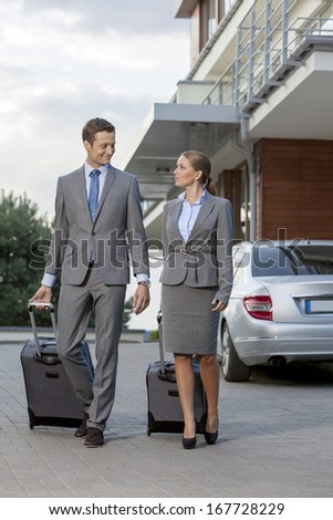 Full-length of business couple with luggage walking outside hotel - stock photo
