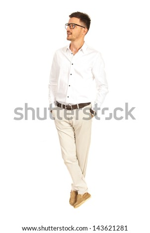 Full length of business man standing with legs crossed looking away to copy space isolated on white background