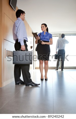 Full length of business people talking in office hallway - stock photo
