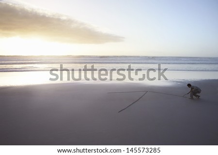 Full length of businessman drawing arrow in sand on beach - stock photo