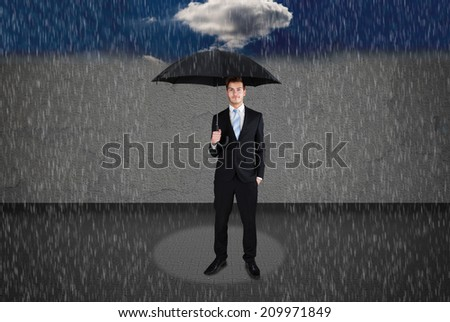 Full length of businessman holding umbrella under rain