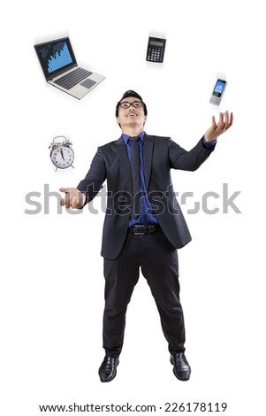 Full length of businessman juggling four items of business tools in studio - stock photo