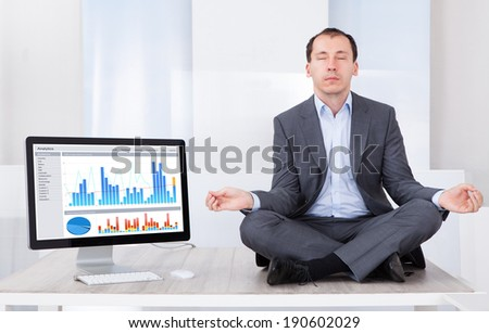 Full length of businessman mediating by computer on desk in office - stock photo