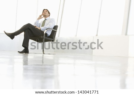 Full length of businessman sitting on chair while looking up in spacious room