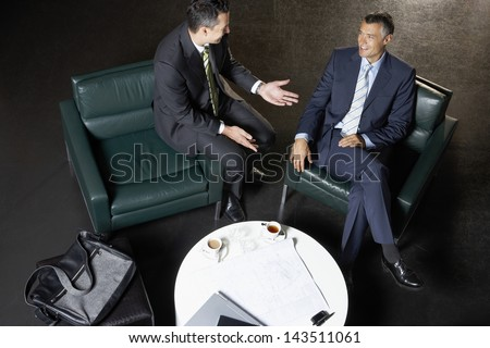 Full length of businessmen sitting on couches discussing at coffee table - stock photo