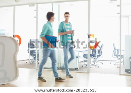 Full-length of businessmen walking at creative work space - stock photo