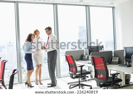 Full length of businesspeople discussing in office - stock photo