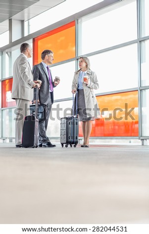 Full length of businesspeople talking on railroad platform - stock photo