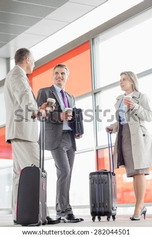 Full length of businesspeople with coffee cups talking on railroad platform - stock photo