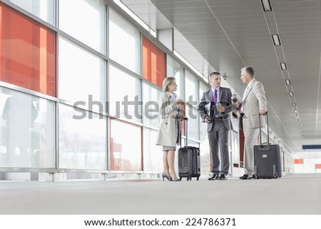 Full length of businesspeople with luggage talking on railroad platform - stock photo