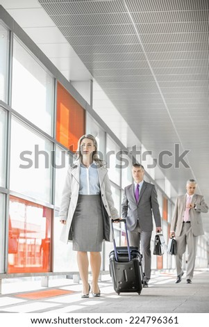 Full length of businesspeople with luggage walking in railroad station - stock photo