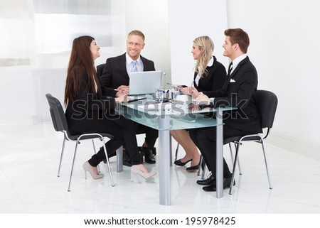 Full length of businesspeople working at desk in office