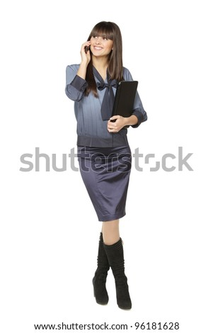Full length of businesswoman standing with laptop talking on mobile phone, isolated on white background - stock photo