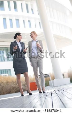 Full-length of businesswomen conversing outside office building - stock photo