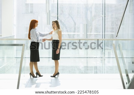 Full-length of businesswomen shaking hands at office hallway - stock photo