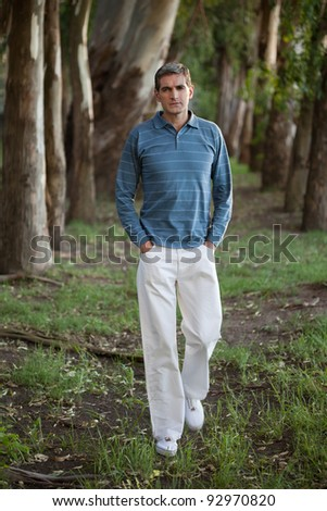 Full length of casual middle aged man walking alone through the woods