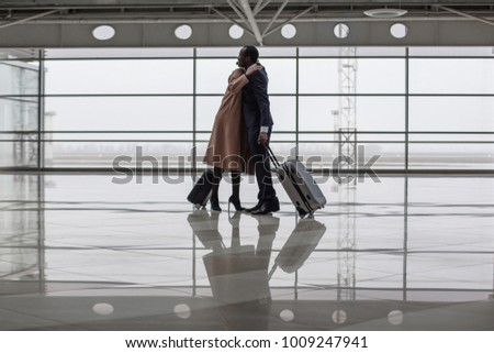 Full length of charming businesswoman and businessman are greeting each other at terminal lounge. They are standing with suitcases and hugging