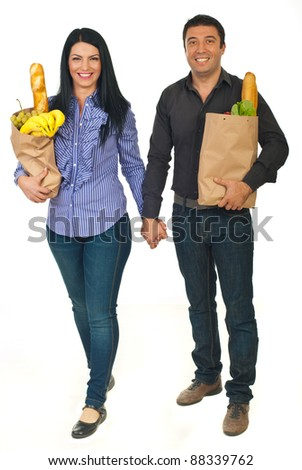 Full length of cheerful couple holding hands and carrying bags with food isolated on white background - stock photo