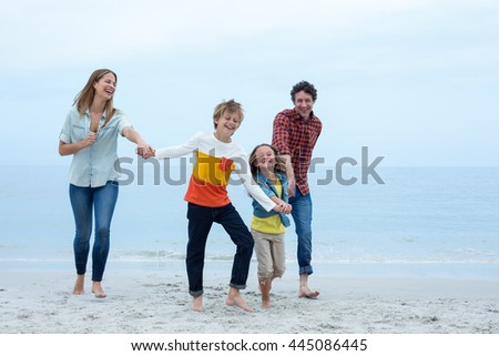 Full length of cheerful family holding hands while running at sea shore - stock photo