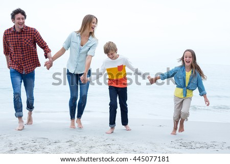 Full length of cheerful family holding hands while walking at sea shore - stock photo