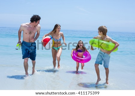 Full length of cheerful family running in shallow water with swimming equipment - stock photo