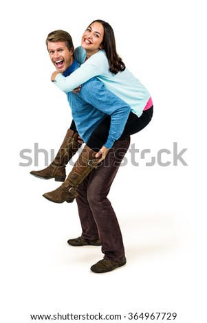 Full length of cheerful man carrying girlfriend on back against white background