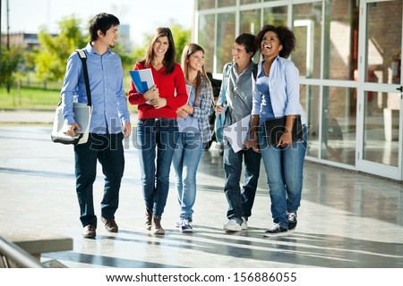 Full length of cheerful university students walking on campus - stock photo