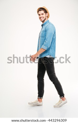 Full length of cheerful young man walking and smiling over white background - stock photo